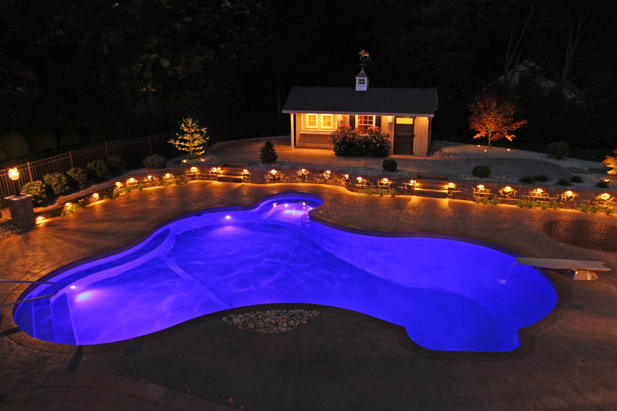 This is a photo of a custom inground pool with purple backlighting at night.