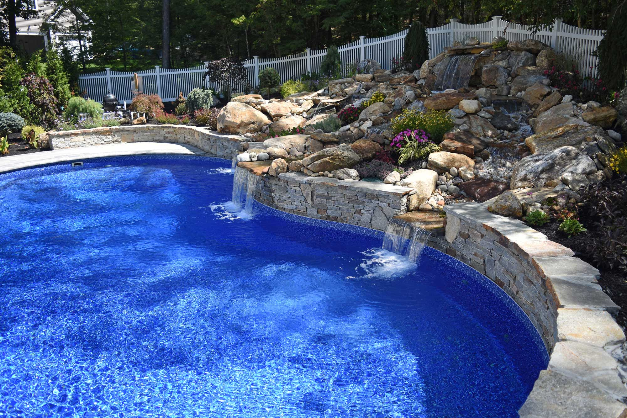This is a photo of a custom inground swimming pool with two waterfalls.
