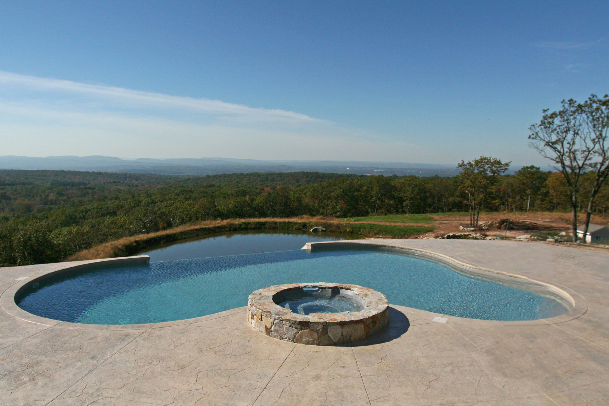 This is a photo of a custom inground swimming pool built by Julianos pools with a spillover spa.